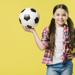 Girl holding soccer ball in front of yellow background