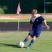 men's soccer player takes a corner kick