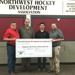 Don Hydukewich the president of North West Hockey Development and the club's treasurer Hugh Martin present Battlefords North Stars head coach and general manager Kevin Hasselberg and board president Troy Slywka with a donation for $10,000 through funds ra