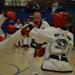 Black belt taekwondo woman performing a roundhouse kick while sparring