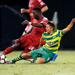 Sergio Manesio sliding for a tackle with a Tampa Bay Rowdies player doing the same thing