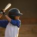 Young boy standing in batting stance with helmet on