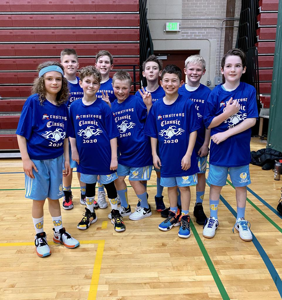 Mpls Lakers Youth Traveling Basketball Program Inc Boys 5th Grade Blue pose with their T-Shirts after becoming the Champions at the Armstrong Classic tournament in Robbinsdale, MN