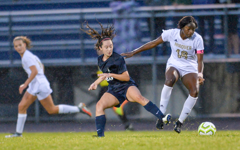 Andover's Brisha Musungu (18) and Totino-Grace's Emilie Ling (20) battle for the ball on a rain-soaked field Friday night at Totino-Grace. The Eagles and Huskies played to a 1-1 tie. Photo by Earl J. Ebensteiner, SportsEngine