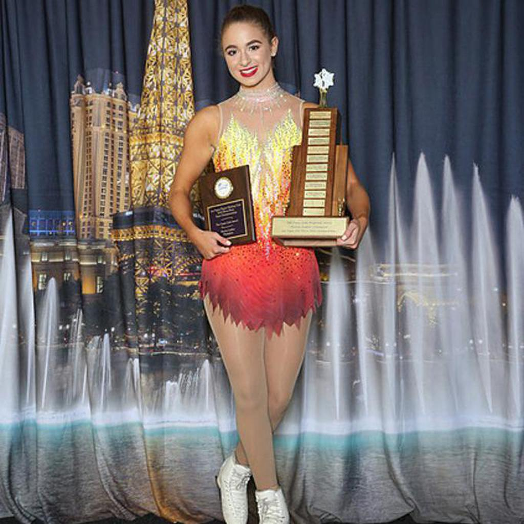 Smiling figure skater posing with her trophies