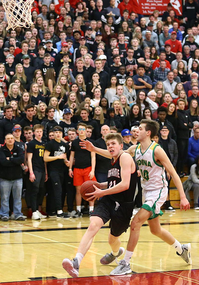 Eden Prairie sophomore John Henry (31) drives the lane past defender Jack  Middleton (