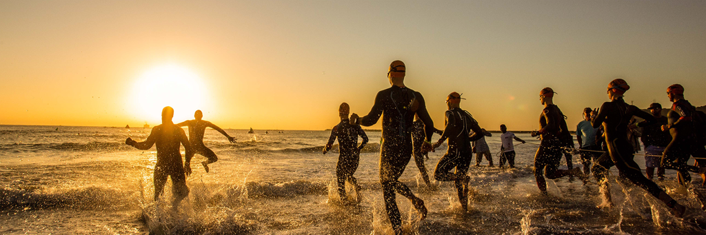 IRONMAN 70.3 Durban athletes are running into the Indian Ocean at uShaka Beach near the Durban Harbour at sunrise