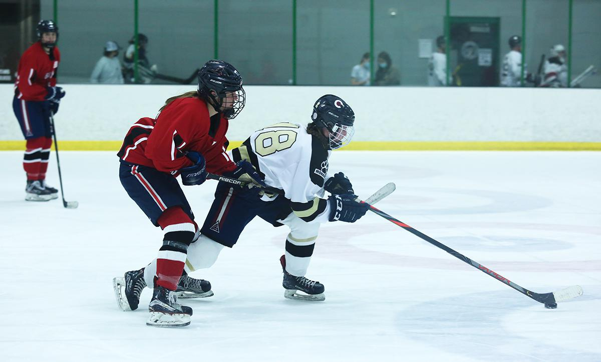 Seneca Urban of the Coyotoes dashes up the ice with a Black Widows defender trailing. Urban recorded an assist in the first period in her team's 2-0 defeat of the Black Widows Friday evening. Photo by Katie Hinkle, SportsEngine