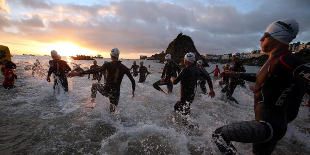 Triathletes entering water for swim