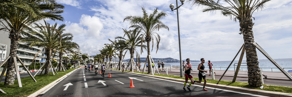 Athletes are running on the Promenade de Anglais along an avenue of palm trees and next to the beach at IRONMAN 70.3 Nice
