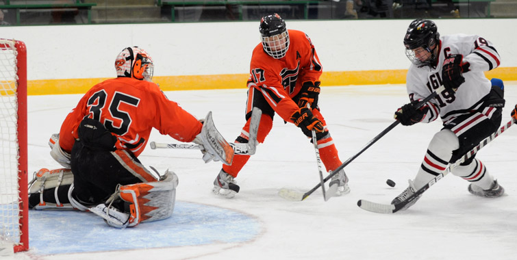 Eden Prairie's John Sullivan, right, tried to control a bouncing puck as Grand Rapids defenseman Curtis Simonson (17) provides support for Thunderhawks goaltender Hunter Shepard. Photo by Loren Nelson
