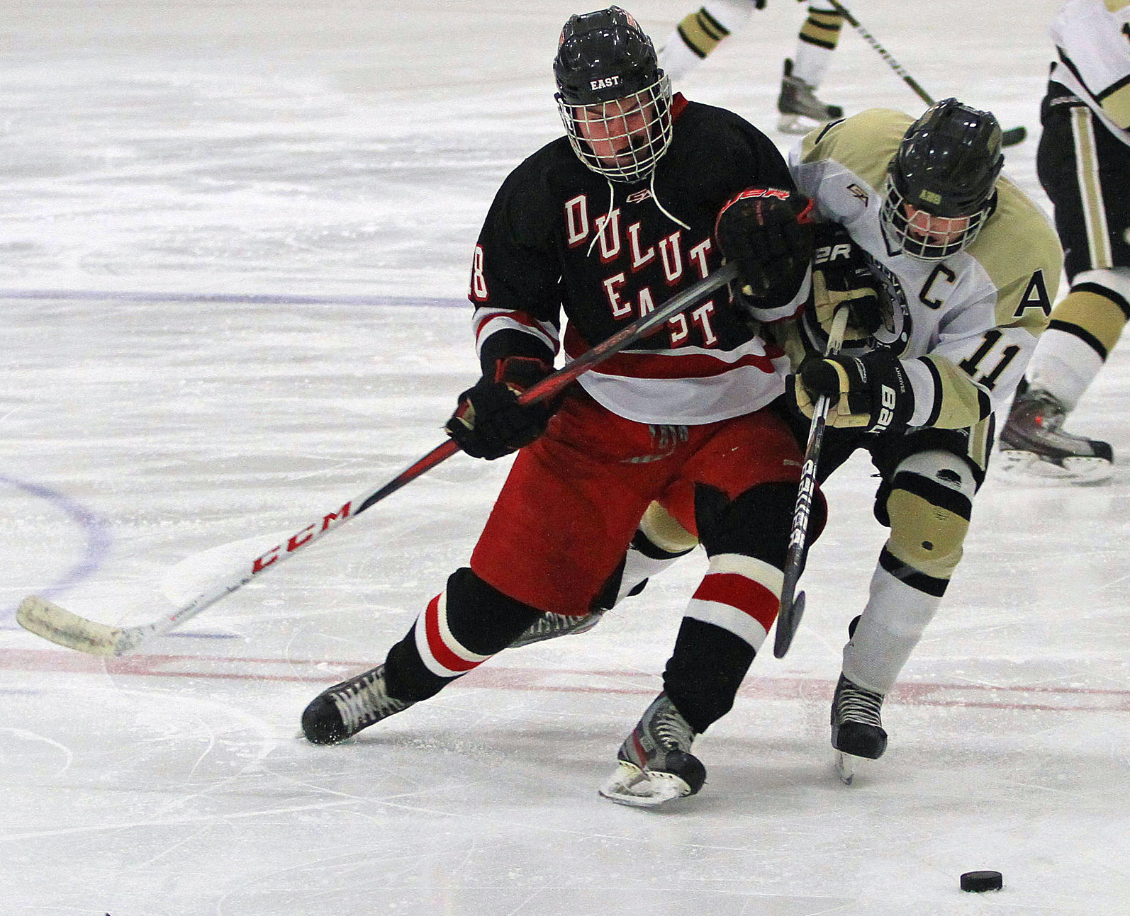 Duluth East's Wyatt Irwin leans into Andover's Brady Barthold as they chase the puck. Photo by Dave Madsen, www.facebook.com/spbdm
