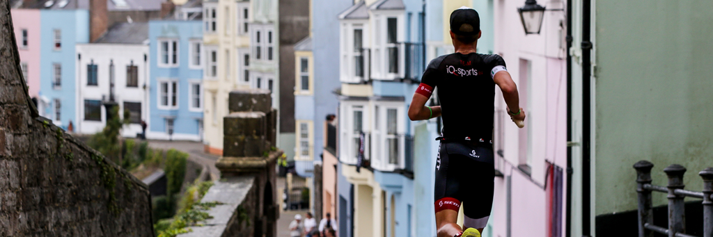IRONMAN Wales athletes running through the medieval town walls and picturesque beachfront