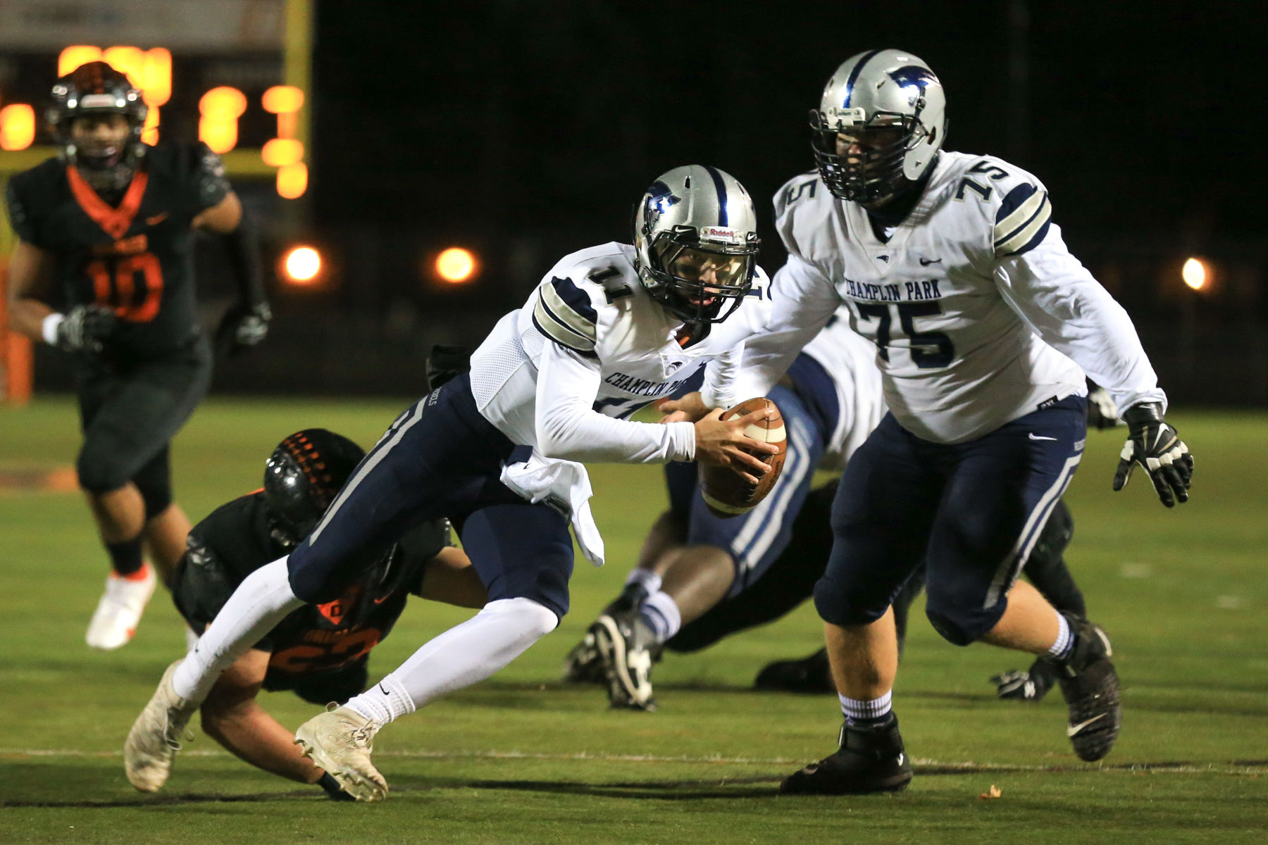 Champlin Park quarterback Cade Fitzgerald scrambles for positive yardage against Osseo Thursday night. The Rebels defeated the Orioles 14-7 in Osseo. Photo by Jeff Lawler, SportsEngine