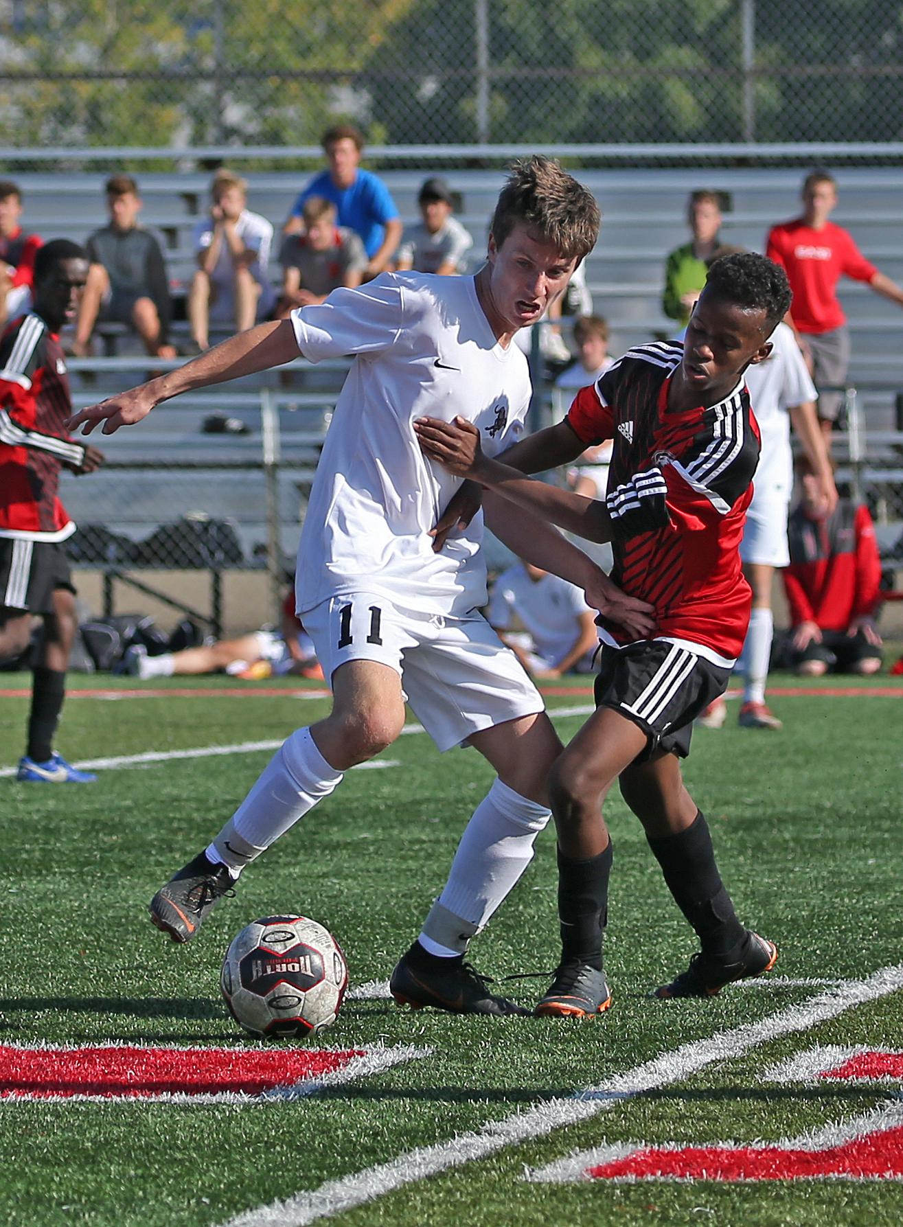 Midfielder Seth Hoffman (11) works the ball around defender Jebril Mohammed. Hoffman connected on a penalty kick in the first half to tie the score at one. Photo by Cheryl Myers, SportsEngine