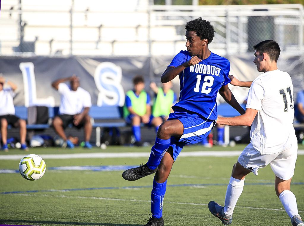 Woodbury junior Joseph Haile (12) sends the ball away from East Ridge defender Zack Kraus (11). Haile set up the Royals' only goal on a rush late in the first half that would send the game into halftime tied 1-1. Photo by Cheryl A. Myers, SportsEngine