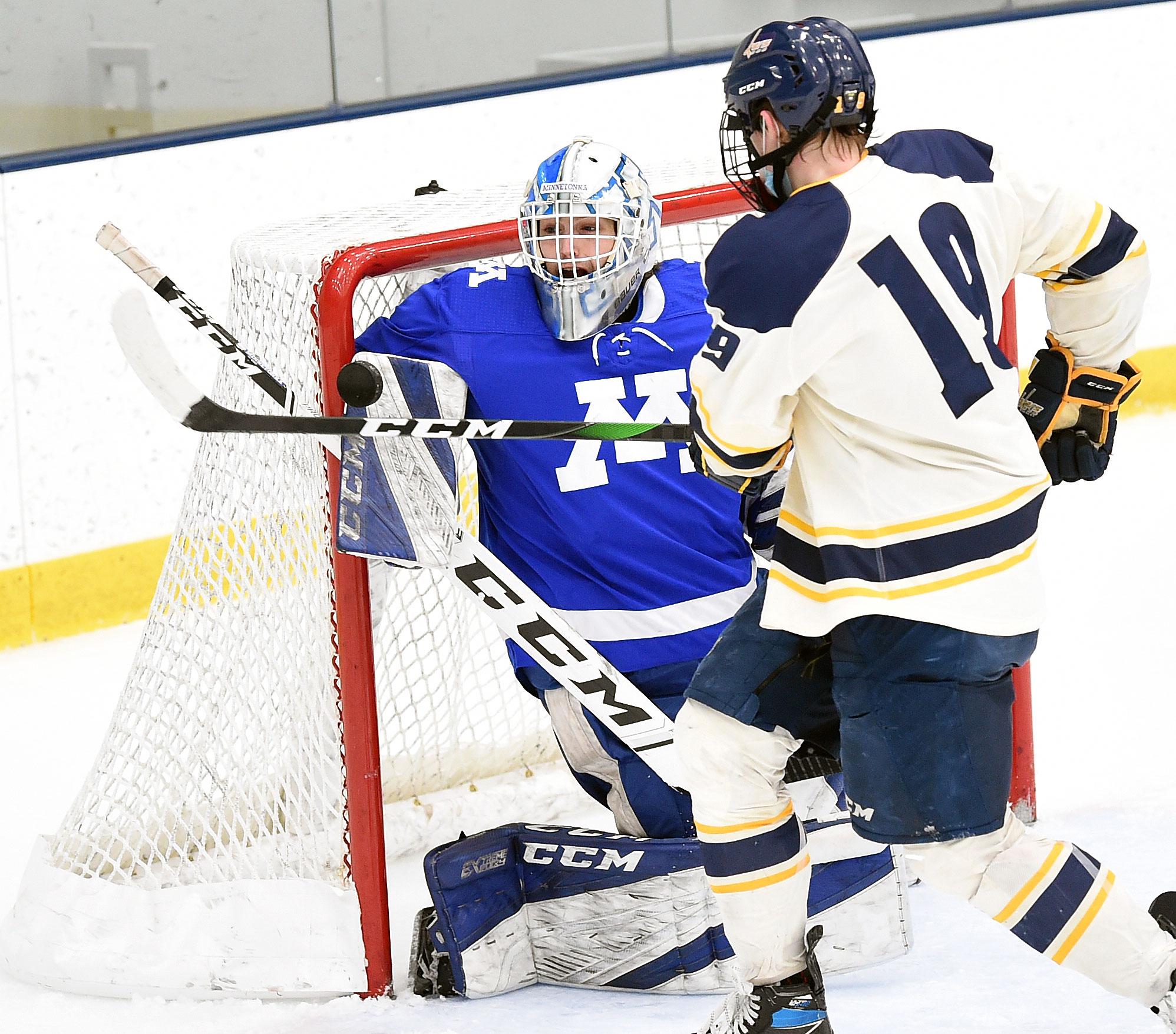 Minnetonka goaltender Kyle Briesemeister makes a second-period save in front of Prior Lake's Alex Bump. Photo by Loren Nelson, SportsEngine