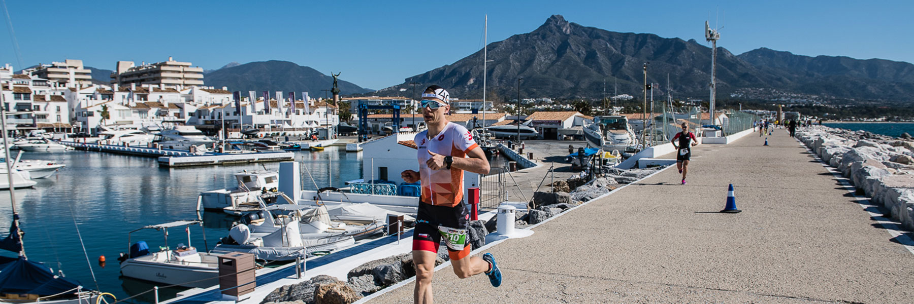 IRONMAN 70.3 Marbella athletes running along the promenade of Marbella which is surrounded by boats