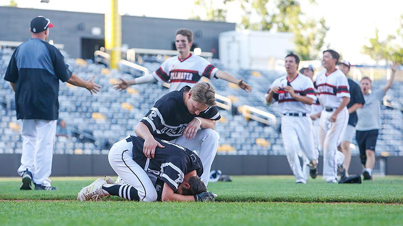 Roseville's Nick Kulseth is consoled by a teammate after making the game's final out. Stillwater players celebrate their Class 4A, Section 4 championship in the background. Photo by Mark Hvidsten, SportsEngine