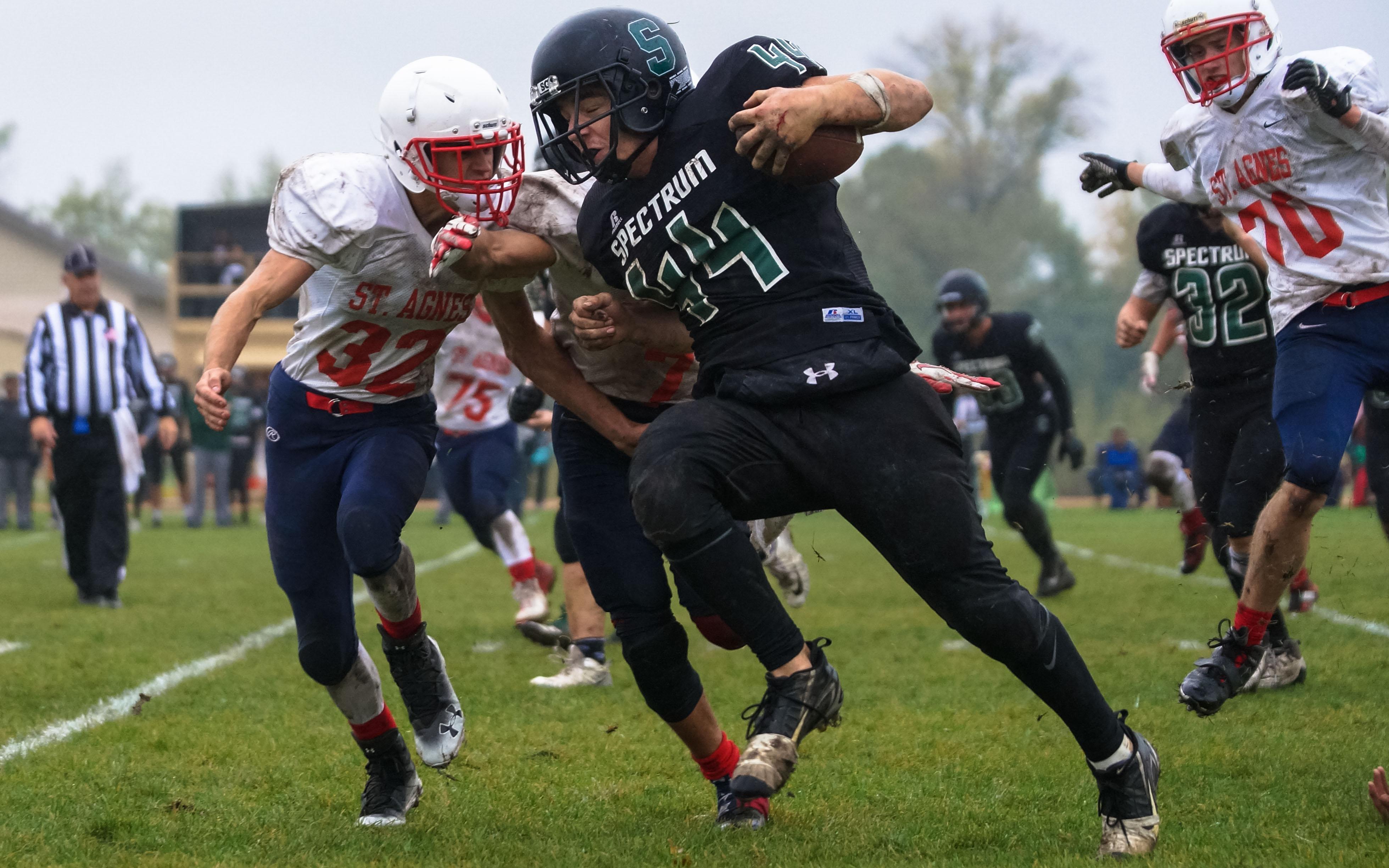 Sting runner Sam Cooper shields the football from St. Agnes attackers Friday in Elk River. Photo by Korey McDermott, SportsEngine