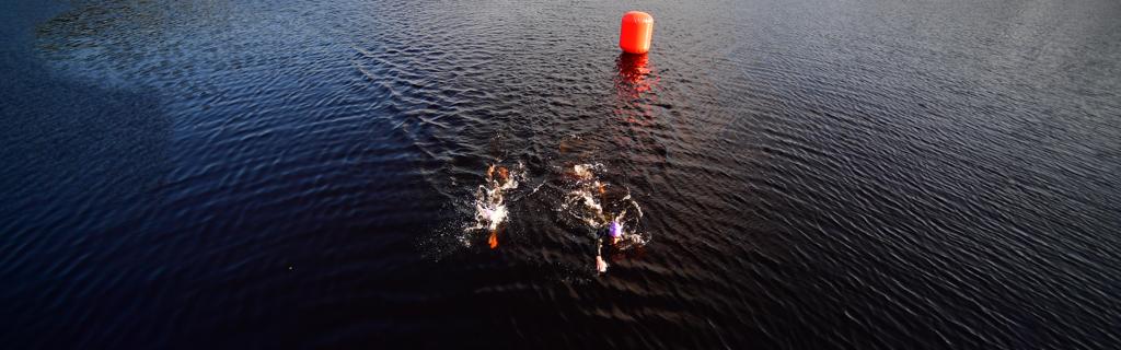 Athletes swimming in Syväri lake in the protected Tahko Bay in Finland