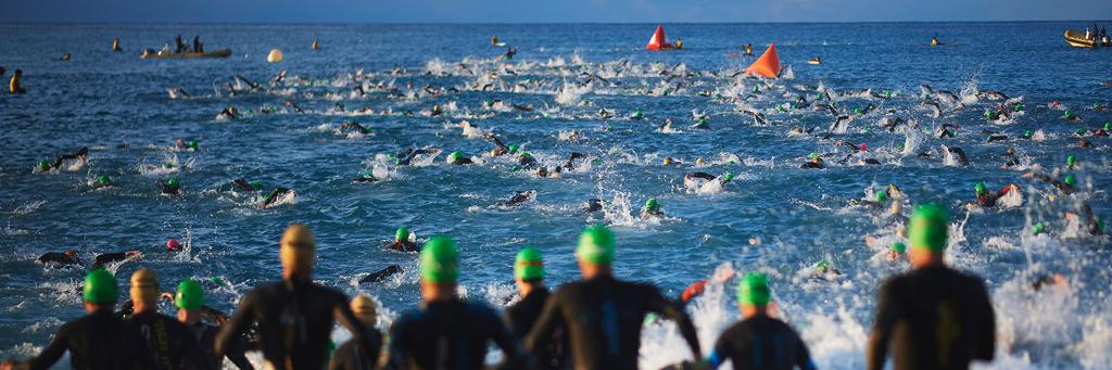 IRONMAN 70.3 Barcelona athletes are swimming in the Mediterranean Sea at Calella beach while more athletes are behind them and waiting to get into the water