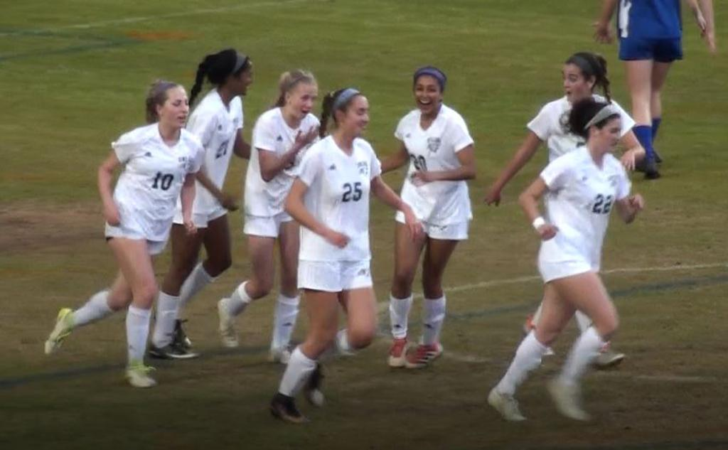 women's soccer team celebrates a goal