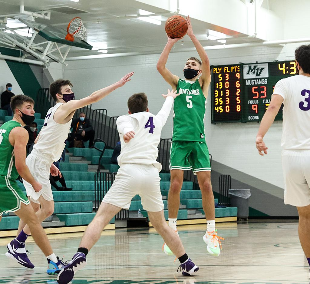 Kobe Kirk (5) shoots from the top of the key over the arms of Cretin-Derham Hall defenders. Kirk led all scorers with 20 points, including four three-pointers, in a 64-51 victory at Mounds View High School. Photo by Cheryl A. Myers, SportsEngine