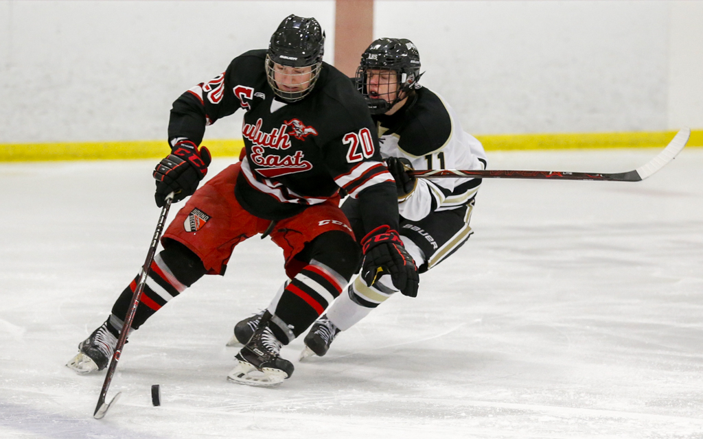 Duluth East senior Frederick Paine battles for control of the puck with Andover's Hunter Jones. The Greyhounds fell to the Huskies 2-1 in overtime Saturday afternoon. Photo by Jeff Lawler, SportsEngine