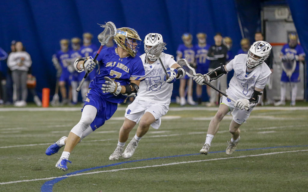 Holy Angels senior Jack Hendrickson tries to elude two St. Thomas Academy defenders Friday night. The Stars fell to the Cadets 12-1. Photo by Jeff Lawler, SportsEngine