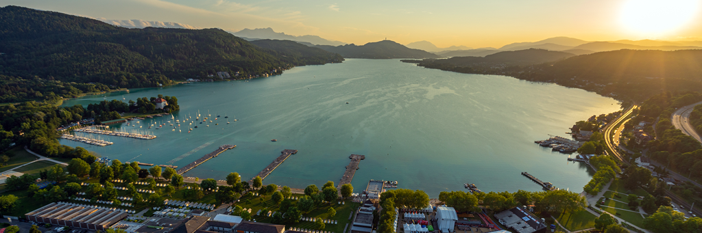 Bird's eye view of Lake Wörth and several cities in Carinthia at sunset with Pyramidenkogel in the background