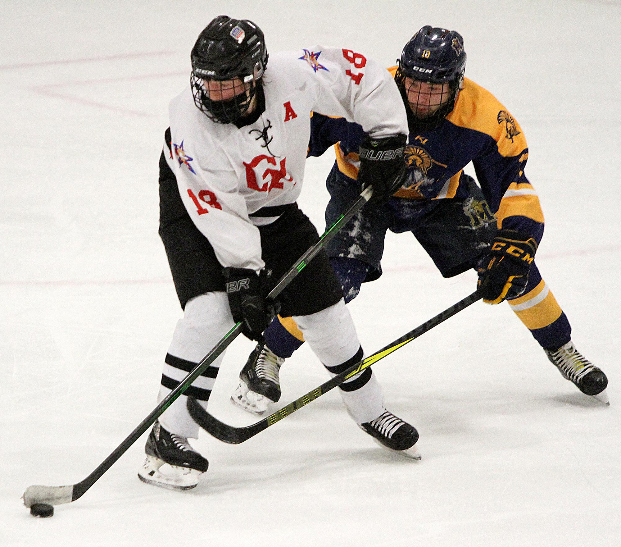 Gentry Academy senior center Nick Sajevic battles for the puck in the neutral zone with Mahtomedi's Ty Decker. Sajevic finished with three goals to lead the Stars to a 7-3 win. Photo by Drew Herron, SportsEngine