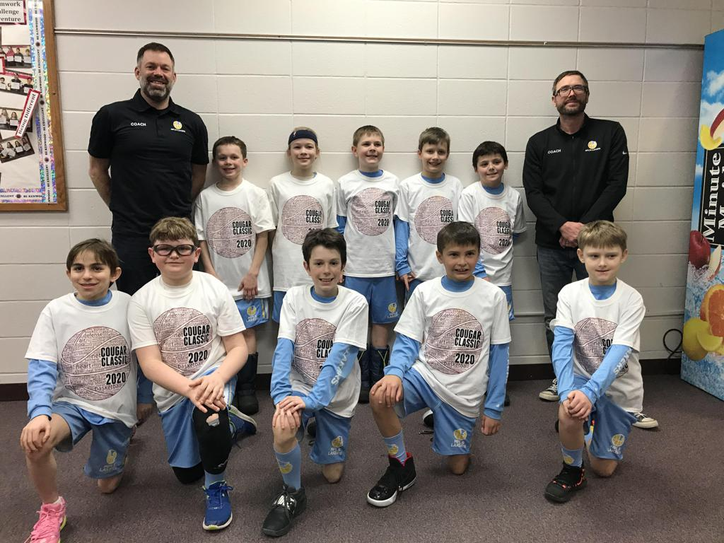 Mpls Lakers Youth Traveling Basketball Program Inc Boys 4th Grade Blue pose with their T-Shirts after becoming the Champions at the Lakeville South Cougar Classic tournament in Lakeville, MN