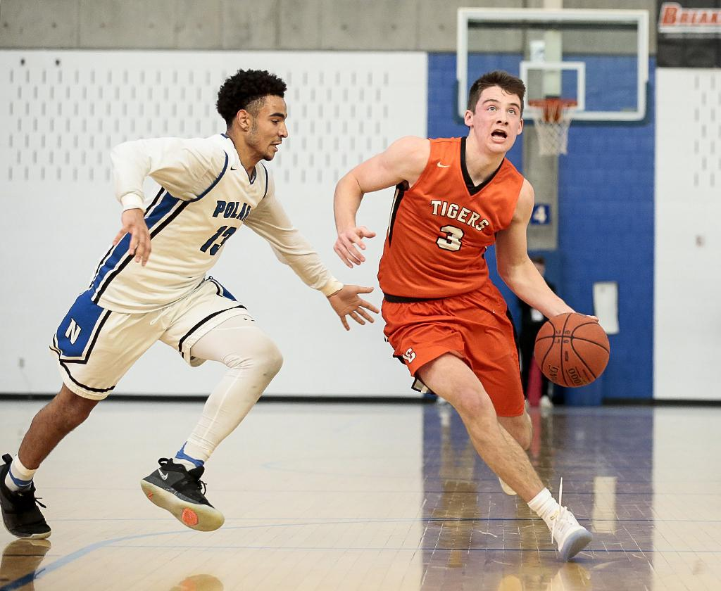Lake City guard Nate Heise (3) drives to the basket past defender Clifford Brown (13). Heise led all scoring with 39 points in the Tigers' 65-54 win over the Polars on Saturday morning. Photo by Cheryl A. Myers, SportsEngine