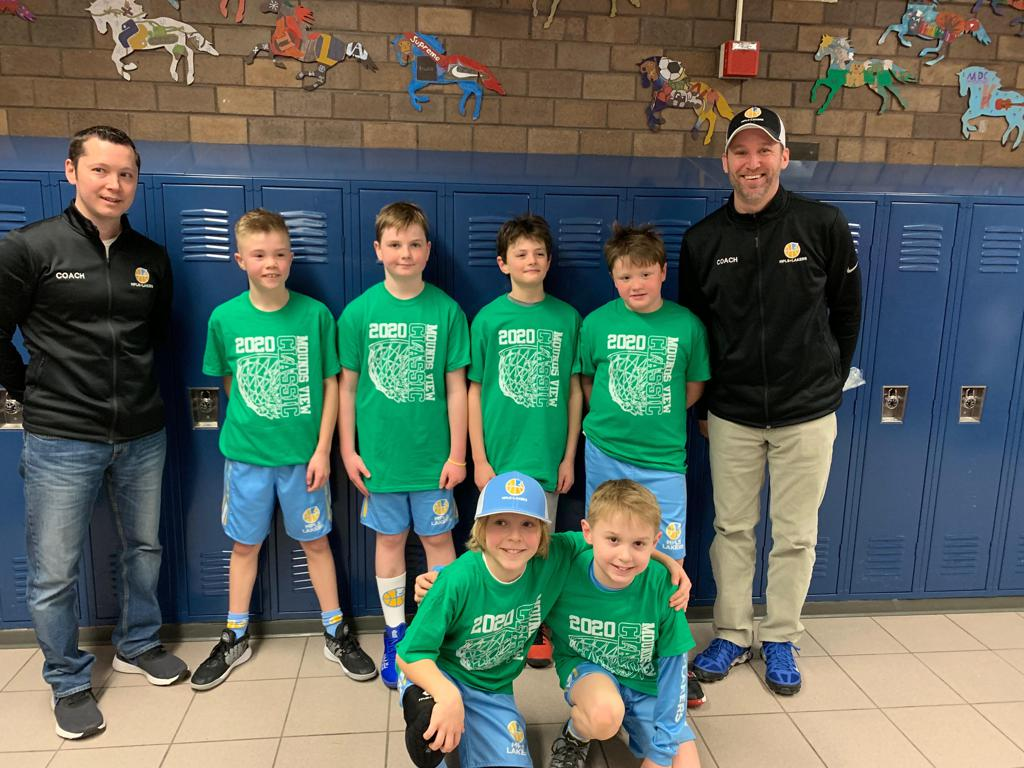 Mpls Lakers Youth Traveling Basketball Program Inc Boys 4th Grade Gold pose with their T-Shirts after becoming the Champions at the Mounds View Classic tournament in Mounds View, MN