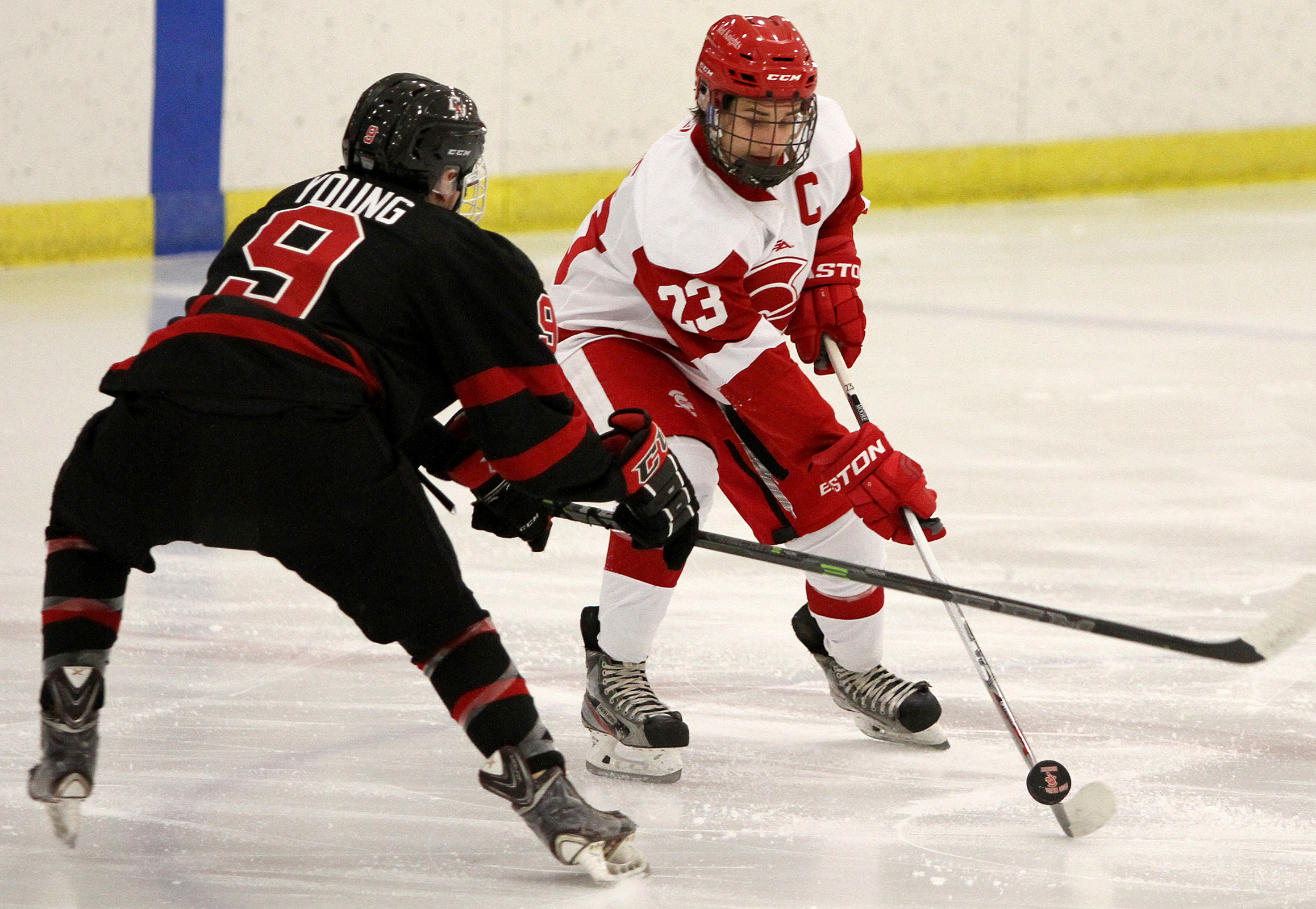 BSM senior Auggie Moore and  Eden Prairie's Wesley Young battle for the puck in the neutral zone in the first period Friday night. Photo by Drew Herron