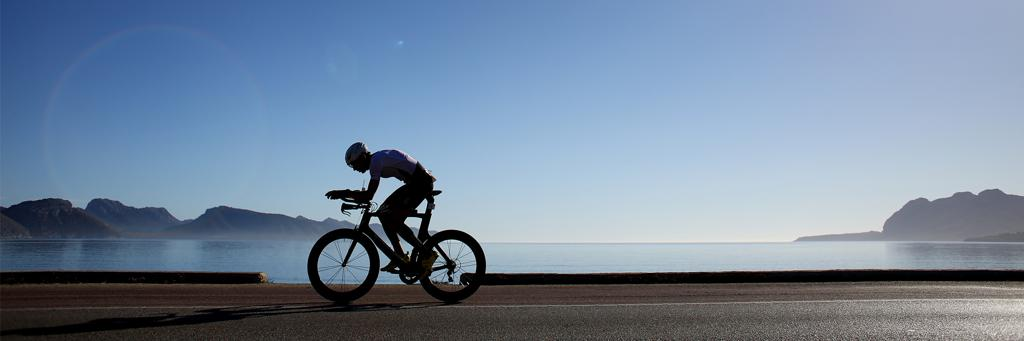 A single athlete who is biking along a street next to the sea on a cloud free and sunny day at IRONMAN 70.3 Mallorca