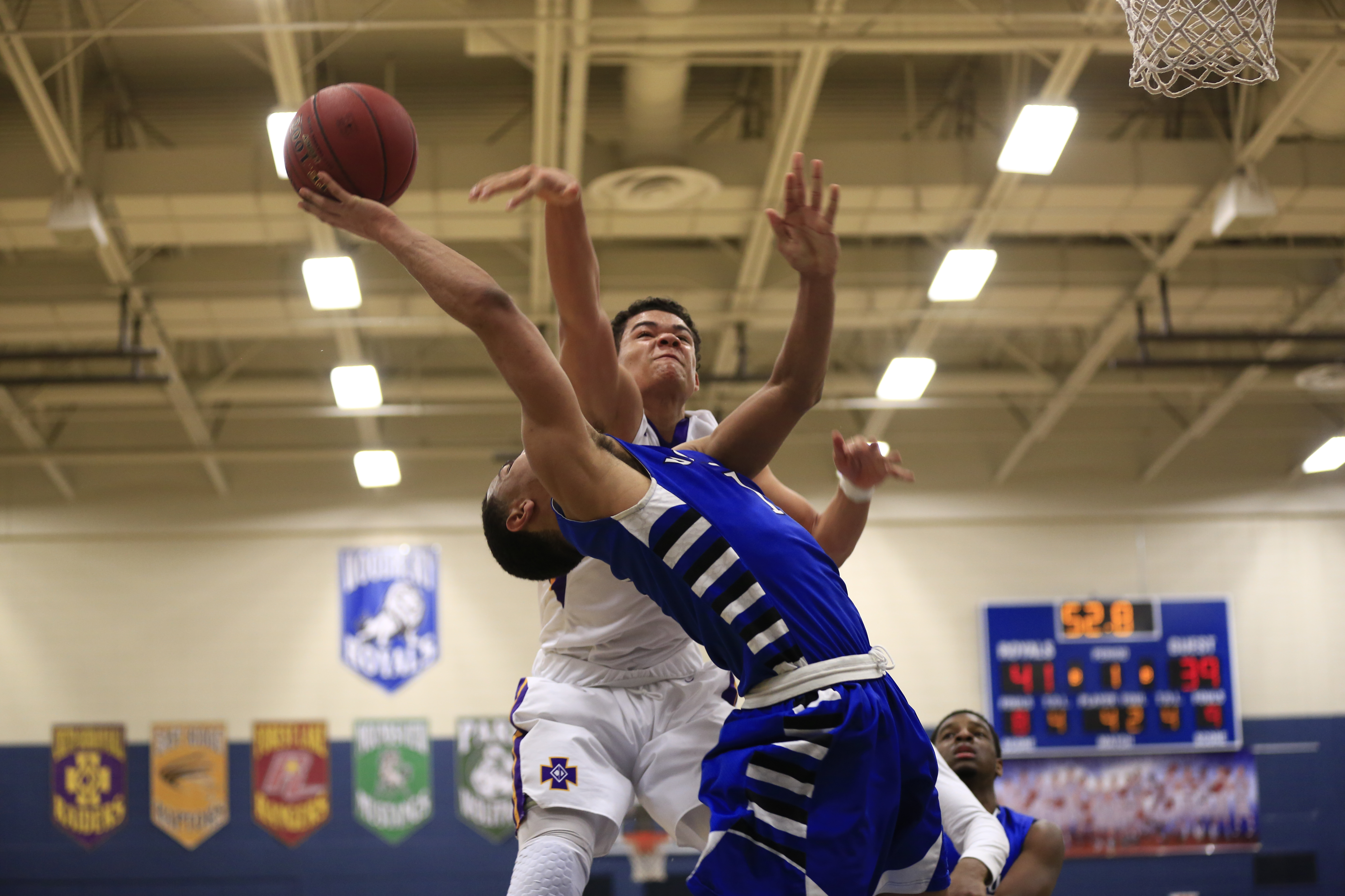 The Royals Jeremiah Coddon (1) attempts to score a basket under the arms of Jake Prince (21) of Cretin-Durham Hall. Jeremiah of the Royals scored 27 points helping his team clinch the victory at home, 85-78. Photo by Chris Juhn
