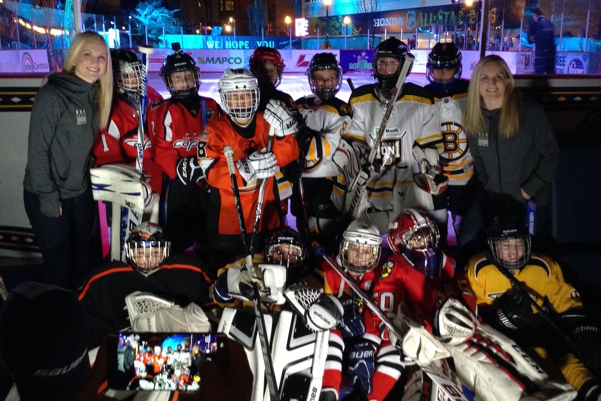 Jocelyne and Monique Lamoureux stop for a picture with youth hockey players ready to hit the ice.
