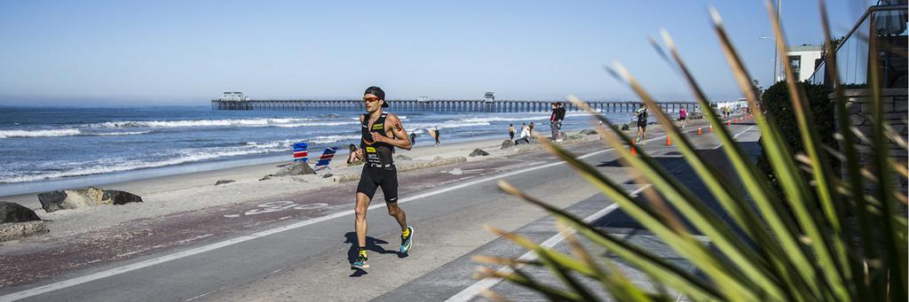 A shoreline runner approaches at IRONMAN Oceanside 70.3