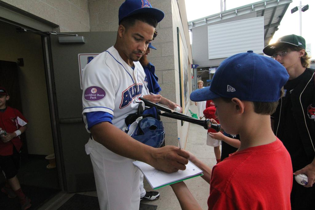 Rockland Boulders player signing autographs for fans.