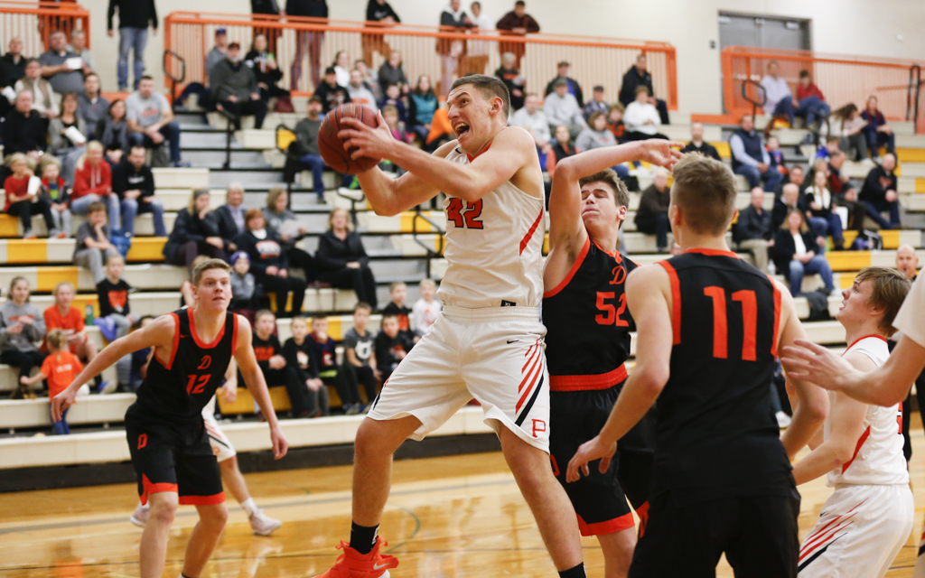 Princeton senior Jon Stimmler pulls down one of his 12 rebounds against Delano Tuesday night. Stimmler also had a team-high 22 points in the Tigers' 76-61 victory. Photo by Jeff Lawler, SportsEngine