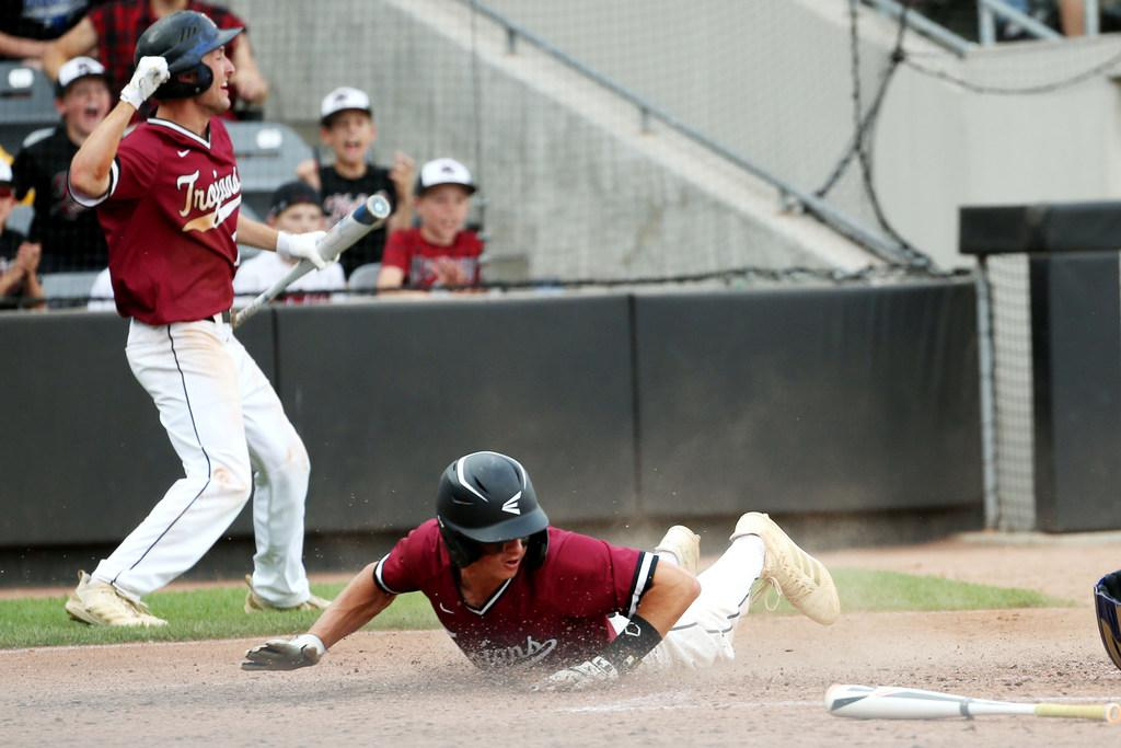 New Prague's Jake Deutsch (1) slides into home plate during the seventh inning to score the game-winning run in a Class 4A quarterfinal against Blaine last spring. Photo by Nicole Neri, Star Tribune