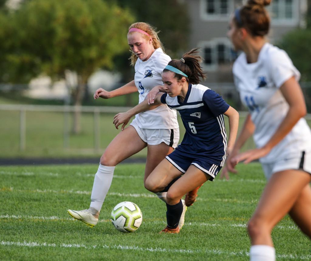 Sophomore Paige Kalal (5) battles for possession with Ella Wade (9) at midfield. Kalal scored her fourth goal of the season late in the first half to tie the game. Photo by Cheryl A. Myers, SportsEngine