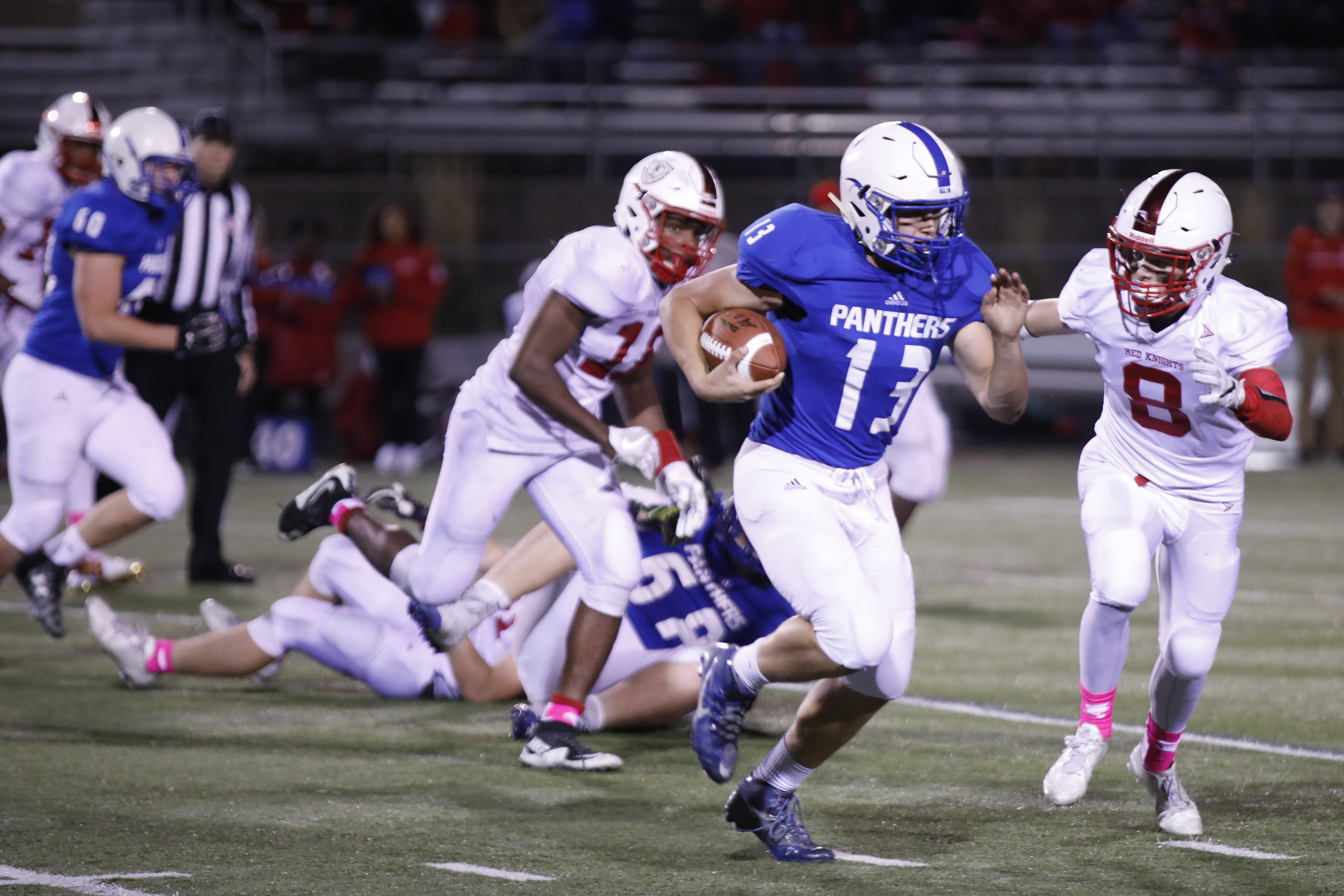 Zachary Ojile (13), QB for Spring Lake Park decided to run the ball while Clyde Sellke (8) of Bernilde tries to tackle him. Zachary scored the final touchdown in overtime to help his team win a 19-13 victory at home. Photo by Chris Juhn