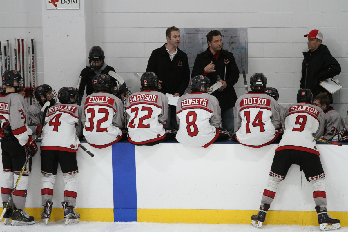 Stillwater boys' hockey players on the bench during a timeout. Photo by Drew Herron, SportsEngine