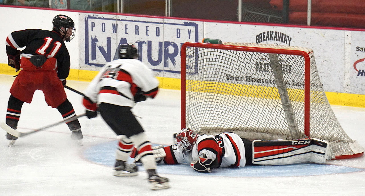 Nick Lanigan of Duluth East beats Elk River's Benny Meyers on a backhand shot in the Hounds' 4-1 loss to the Elks on Saturday. Credit: Peter Odney.