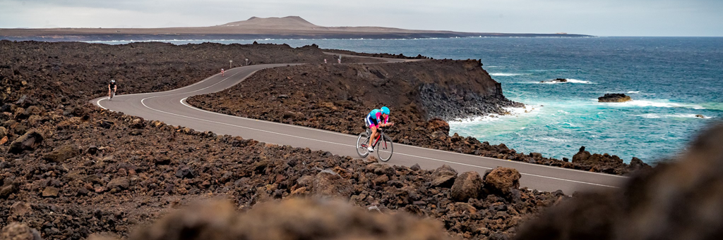 Athletes biking on a street surrounded by black and stark landscape and stunning turquoise sea