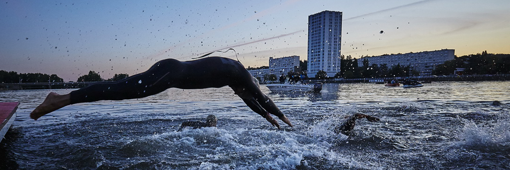 Athlete jumping into Lake Allier at sunrise to join other fellow athletes at IRONMAN Vichy