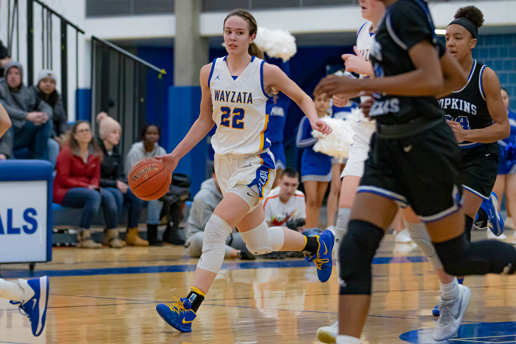 Wayzata junior forward Jenna Johnson (22) brings the ball up the court against Hopkins. Johnson led her team with 28 points but the Trojans fell to the Royals 87-77 on Tuesday night at the Lindbergh Center. Photo by Gary Mukai, SportsEngine